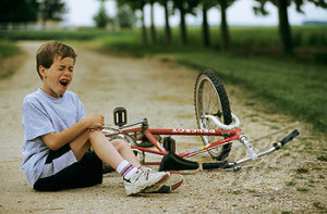 Little boy crying on a path, near his bike